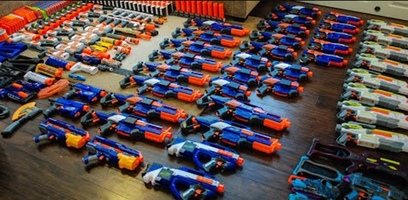 over fifty nerf blasters lined up on the floor